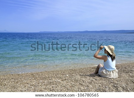 Girl on a pebble beach with hat and sun glasses - stock photo