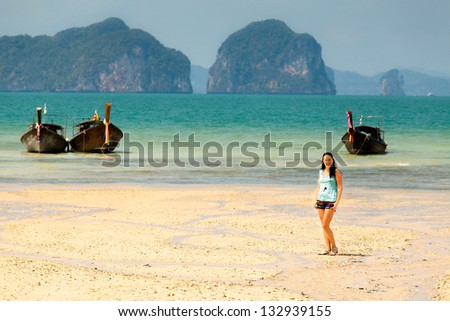 girl on a sandy beach between the mountains and boats in Thailand