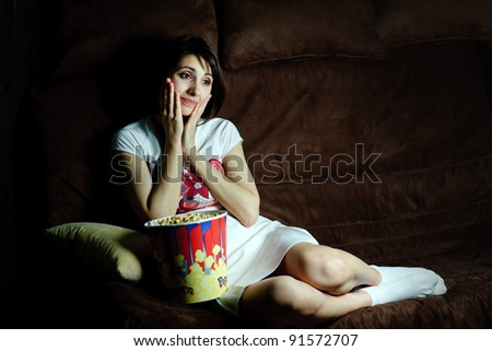 Girl on a sofa watching TV - stock photo