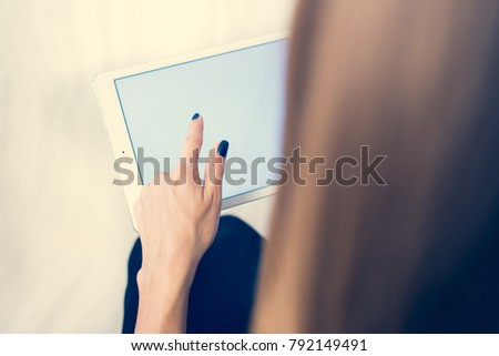 Girl on a tablet computer, browses the information. The white background and the screen