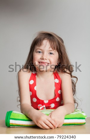Girl on a towel, smiling with baby teeth dropped out - stock photo