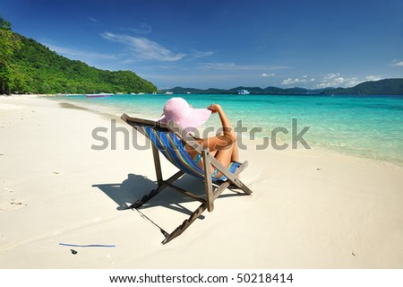 Girl on a tropical beach in chaise lounge - stock photo