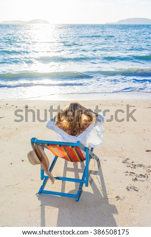 Girl on a tropical beach with a straw  hat - stock photo