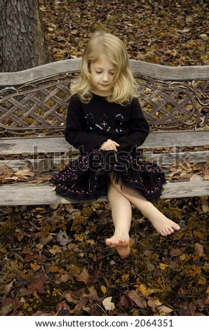 Girl on an antique bench in autumn - stock photo
