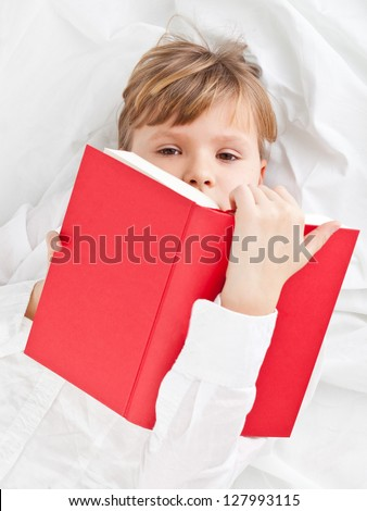 Girl on bed reading book - education or knowledge concept