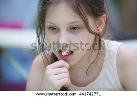 Girl On Bed Taking Pill - stock photo