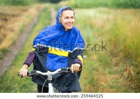 Girl on bike enjoy her riding in rainy day - stock photo