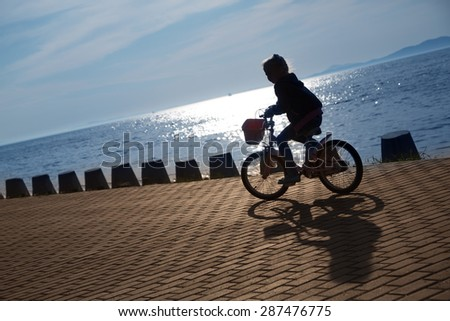 Girl on bike on the seafront promenade at sunset. Focus on the pavement. On image superimposed filter Color Lookup. - stock photo