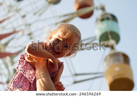 girl on dad hands near the observation wheel. - stock photo