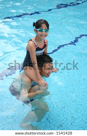 Girl on dad's shoulder in the pool - stock photo