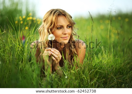 girl on dandelion on green field