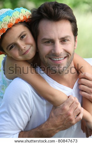 Girl on father's back - stock photo