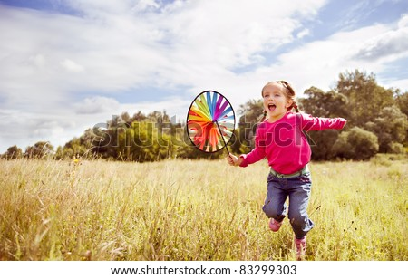 Girl on grass in summer  day holds windmill in hand - stock photo