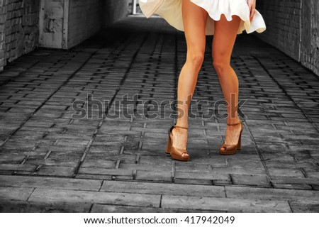 Girl on high heels with beautiful tanned slim sexy legs in a short white dress, spinning in the underpass