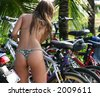 Girl on Ipanema beach picking up her bicycle - stock photo