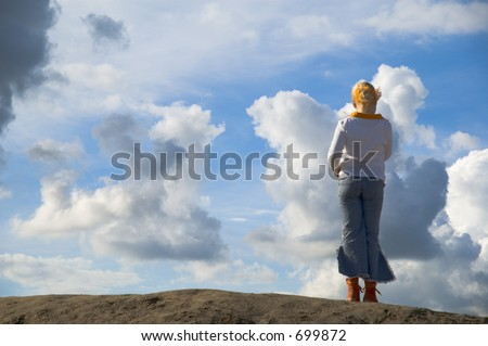 girl on look out on hilltop against sky with big clouds - stock photo