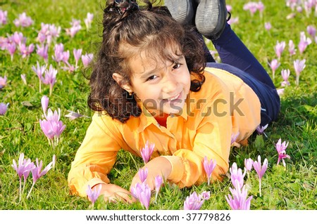 Girl on meadow with pink flowers around