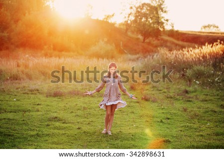 girl on meadow with sunset - stock photo