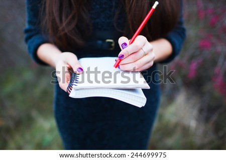 girl on nature writing in a notebook - stock photo