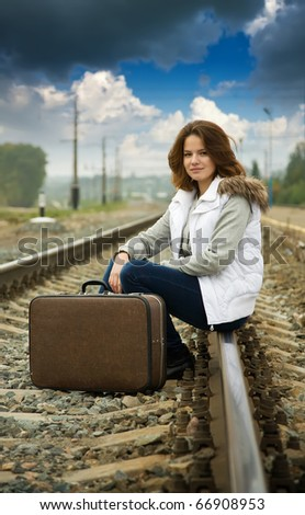 Girl on  railway sitting with her suitcase - stock photo