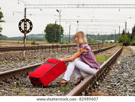 Girl on railway sitting with red  suitcase - stock photo
