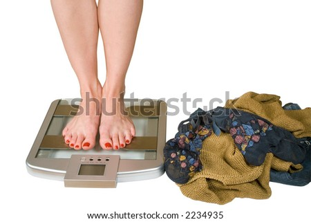 girl on scales and take off clothes - stock photo