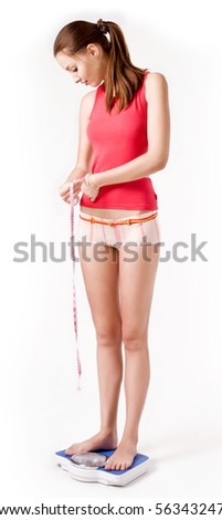 Girl on scales measuring her waist - stock photo