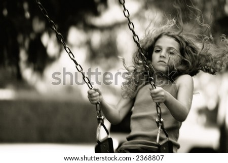girl on swing-set at the playground - stock photo