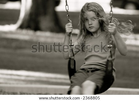 Girl on swing-set in park summertime