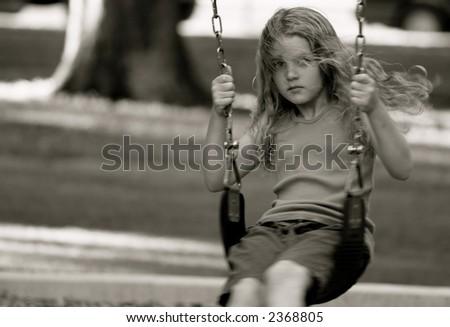 Girl on swing-set in park summertime - stock photo