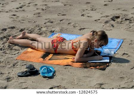 Girl on the beach doing sudoku - stock photo