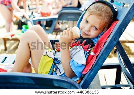 girl on the beach eating an ice cream - stock photo