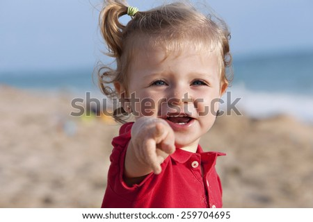 Girl on the beach, pointing - stock photo