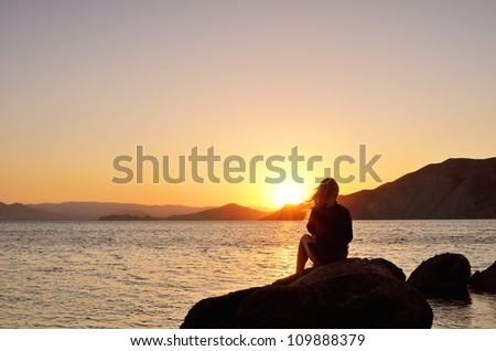 Girl on the beach watching the sunset - stock photo