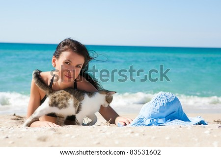Girl on the beach with a kitten and wearing a hat - stock photo