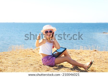 girl on the beach with laptop and phone showing okay - stock photo