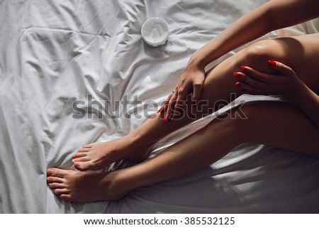 Girl on the bed applaying cosmetic on her legs - stock photo