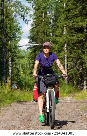 girl on the bicycle in the forest, road sign in the background, Russia, Karelia, 2014 - stock photo
