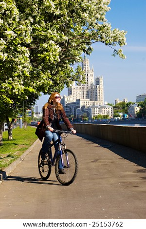 Girl on the bicycle on the Moscow embankment - stock photo