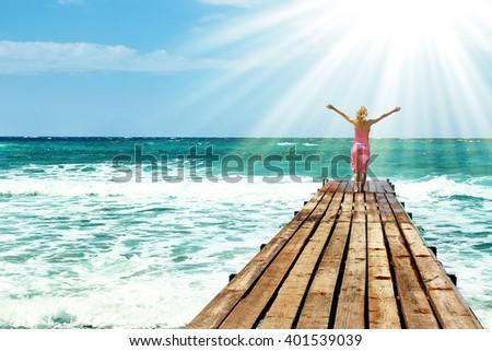 Girl on the bridge pier seashore - stock photo
