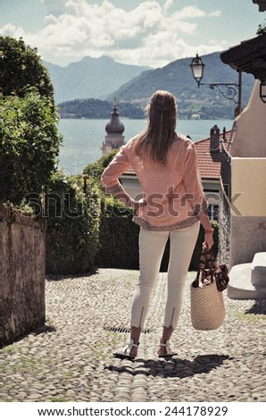 Girl on the cobbled street of Menaggio town. Lake Como, Italy -- retro nostalgic filtered look - stock photo
