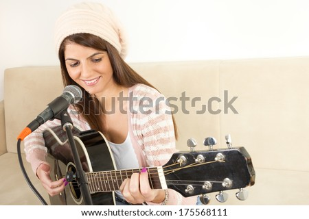 girl on the couch playing guitar and singing on microphone - stock photo