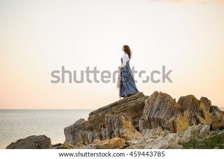 girl on the edge of a cliff looking out to sea, a girl in a long dress at sunset