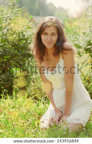 girl on the lawn/girl in white dress sitting on grass and smiling - stock photo