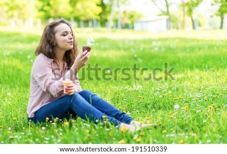 girl on the nature blows bubbles - stock photo