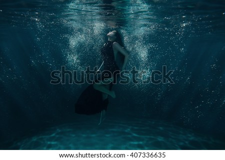 Girl on the ocean floor among the light beams passing through water. - stock photo