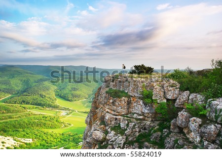 Girl on the peak of mountain. Landscape composition. - stock photo