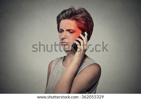 girl on the phone with headache. Upset unhappy female talking on phone isolated grey wall background. Negative human emotion face expression feeling life reaction. Cellular mobile radiation concept - stock photo