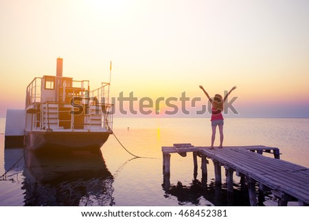 Girl on the pier in the background of the sea, ship and sunset. Ukrainian landscape