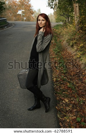 girl on the road waiting for a car - stock photo